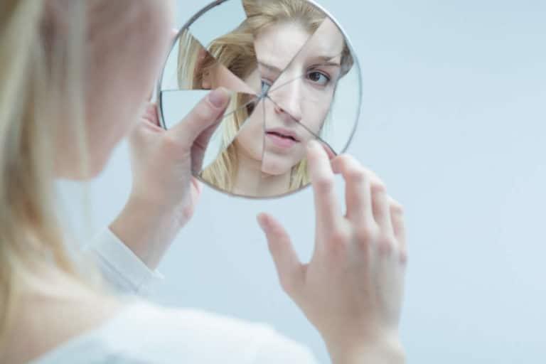 Frau schaut in Spiegel und zweifelt an sich