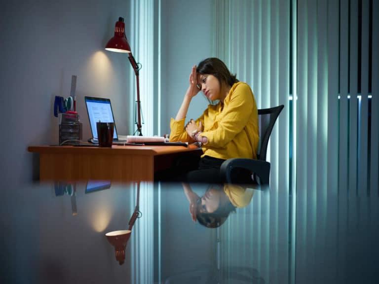 Traurige Frau alleine am Schreibtisch