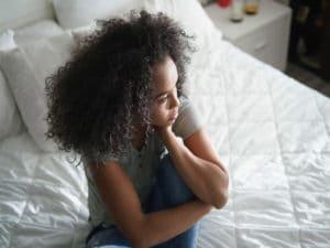 Traurige Frau alleine auf dem Bett